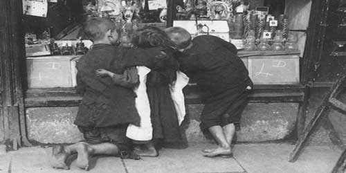 A group of Victorian children, with bare feet, look in a shop window.