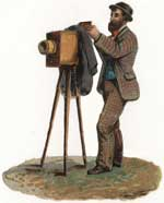 A bearded man stands with a Victorian style camera..