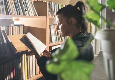 A female student reading a book by a bookcase.