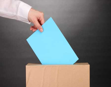 A hand placing a vote into a ballot box.